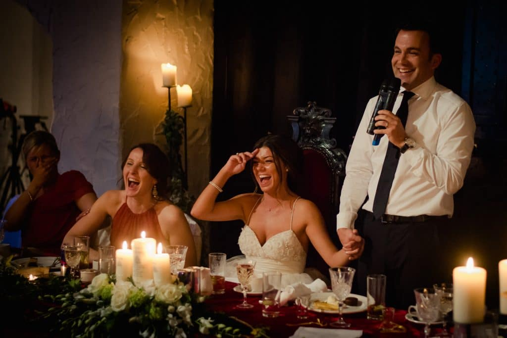 Couple laughing by candle light during wedding speech at Kinnitty Castle