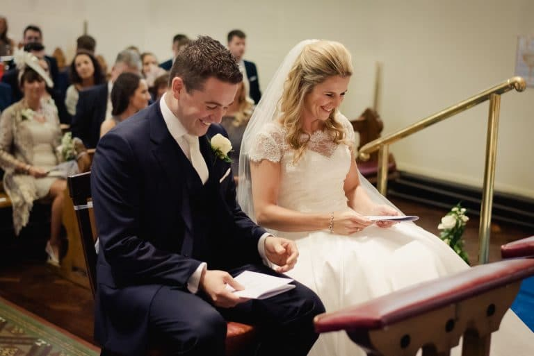 Laughing wedding couple at altar in Cabinteely Church