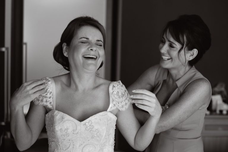 Laughing bride and bridesmaid getting ready