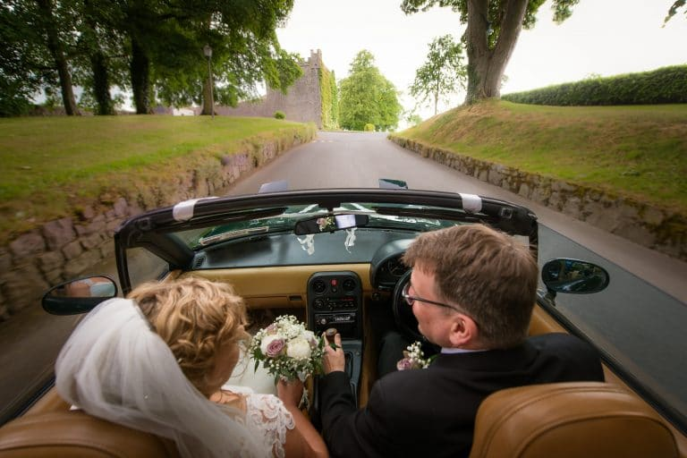 Wedding couple in convertible at Castle Durrow