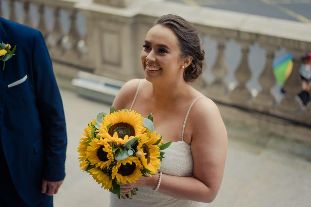 Smiling bride holding sunflowers outside City Hall
