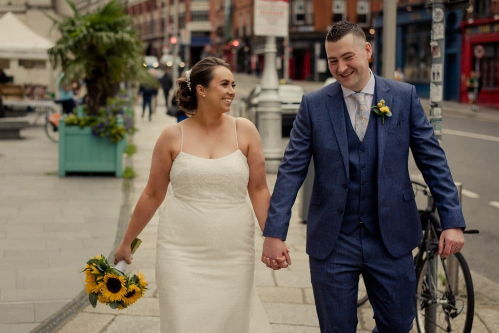 Smiling newlyweds walking in Dublin City