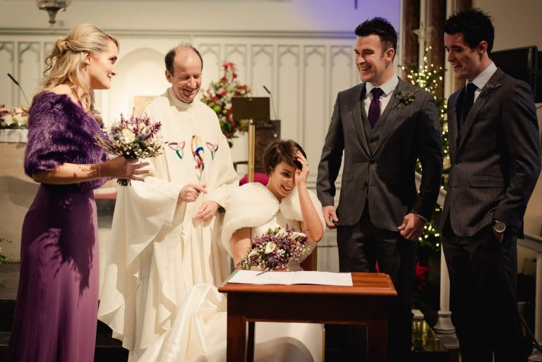 Laughing wedding party signing register in Naas Church