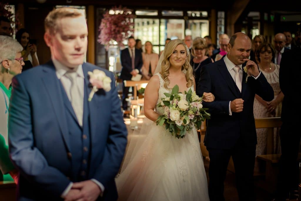 Emotional wedding moment at top of wedding aisle