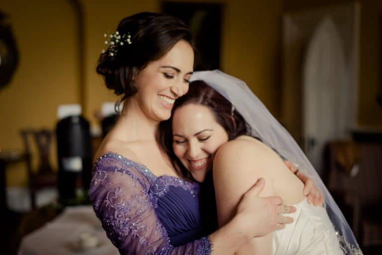 Bride and bridesmaid embracing in Kinnitty Castle