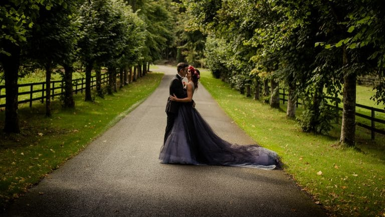 Couple kissing on Kinnitty Castle avenue surrounded by trees