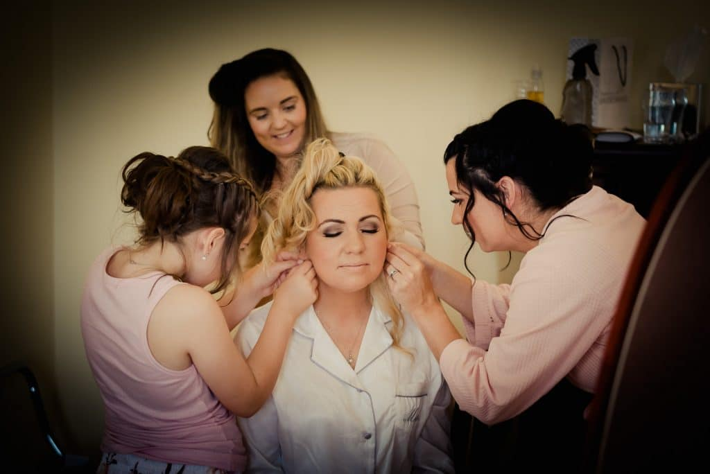 Bride surrounded by people helping her get ready on wedding morning
