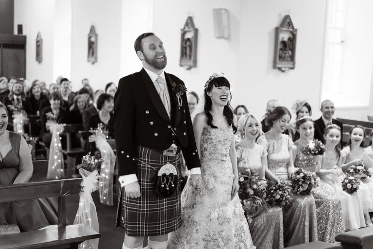 Laughing couple at wedding altar in Kinnitty church