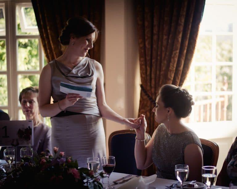Couple touching hands during wedding speech