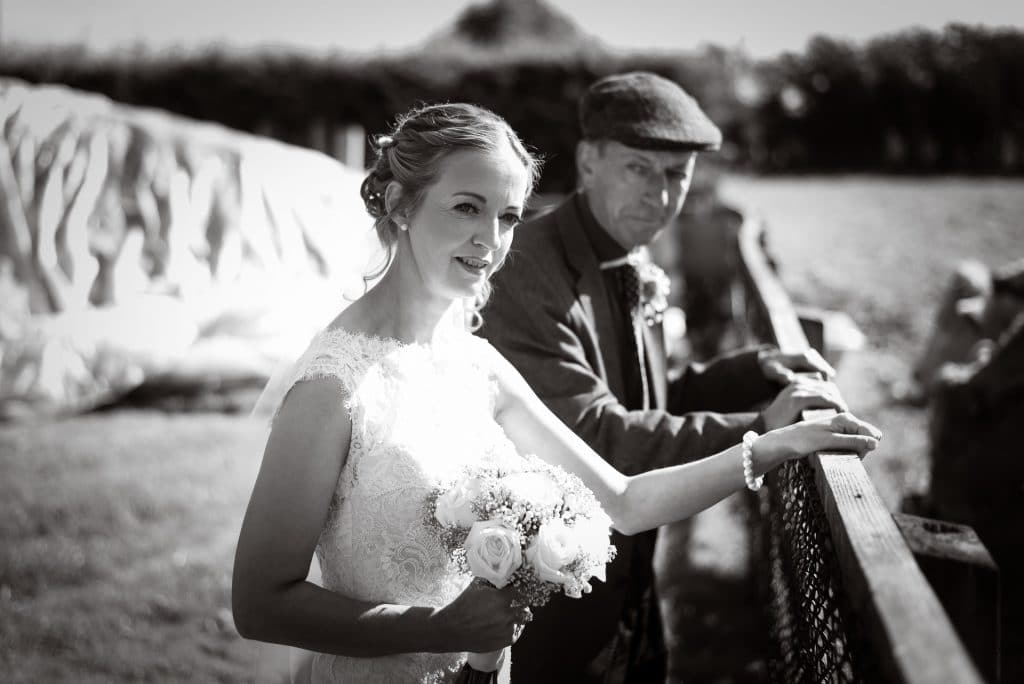 Bride and uncle visiting cattle on wedding morning