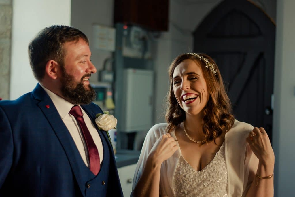 Wedding couple laughing in church vestibule