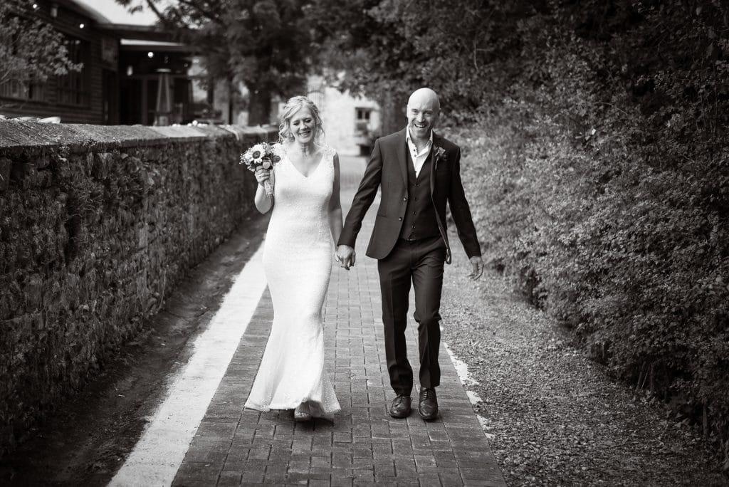 Laughing couple walking to Village Barn Wedding Sanctuary