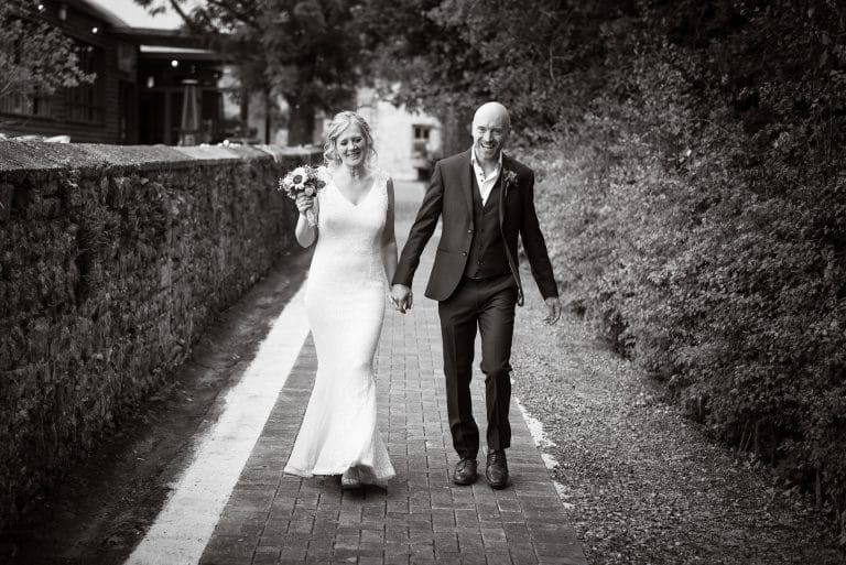 Laughing couple walking to Village Barn Wedding Sanctuary