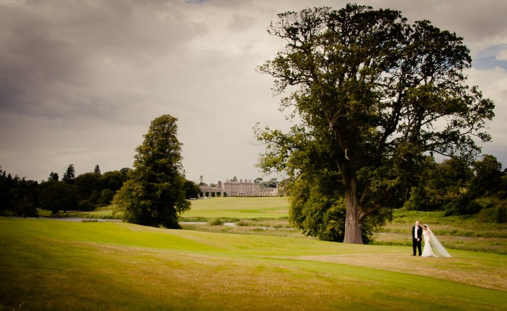 Weddiing couple walking with Carton House in background